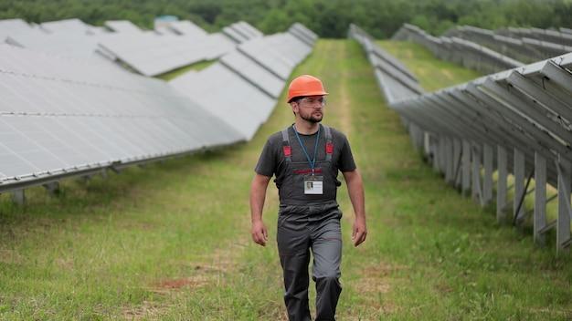 보호용 헬멧을 쓴 전문 남성 엔지니어가 생태학적 태양열 발전소 건설을 하고 있습니다. 전기, 생태, 기술의 개념입니다. 태양 전지 패널의 농장입니다.