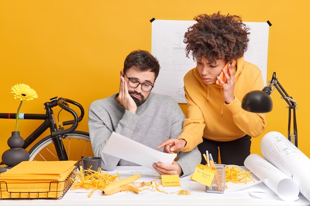 Professional male engineer looks sadly at paper listens explanation from female trainee who talks via smartphone pose at coworking space together. construction workers work on technical plans