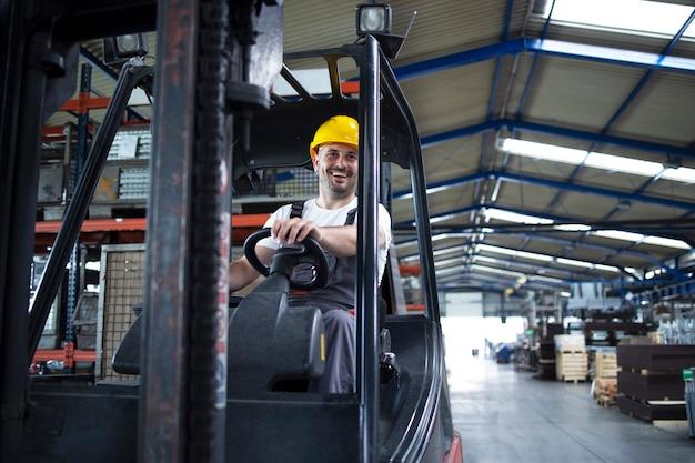 공장의 창고에서 지게차 기계를 운영하는 전문 남성 산업 운전자.