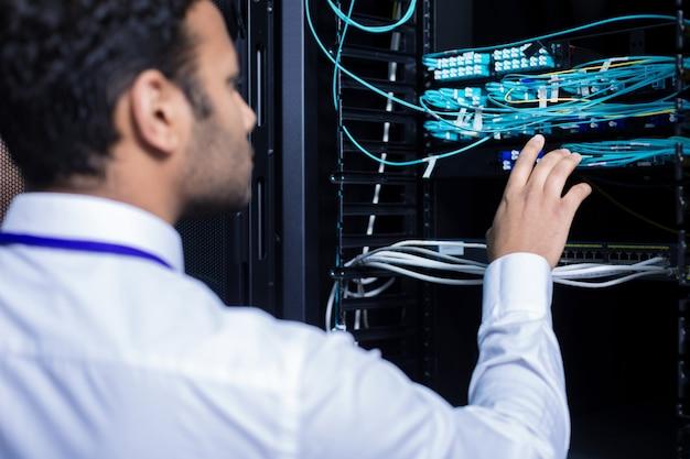 Профессиональный ит-администратор мужского пола стоит перед сетевым сервером и проверяет интернет-кабели, выполняя свою работу