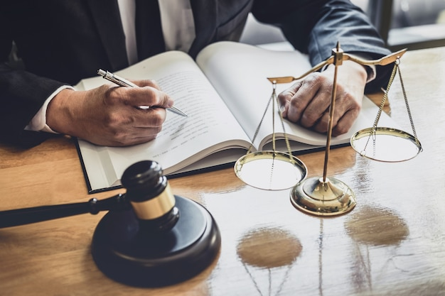 Профессиональный юрист или судья мужского пола, работающий с контрактными документами, документами и молотком и весами правосудия на столе в зале суда, концепция юридических и юридических услуг