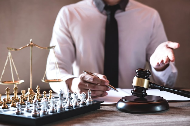 Professional male lawyers working on courtroom sitting at the table and signing papers with gavel