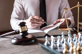 Professional male lawyers working on courtroom sitting at the table and signing papers