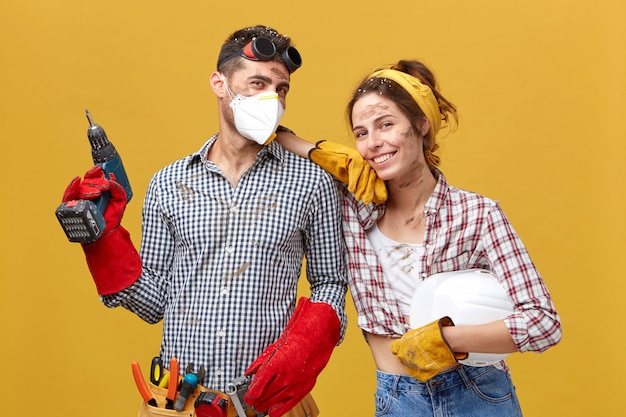 Professional male manual worker wearing protective eyewear on head, mask and gloves holding drilling machine fixing something and his colleague female with dirty face having happy expression