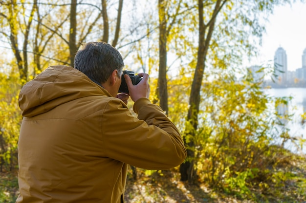 Professional male photographer shooting outdoor in fall yellow forest on modern dslr camera