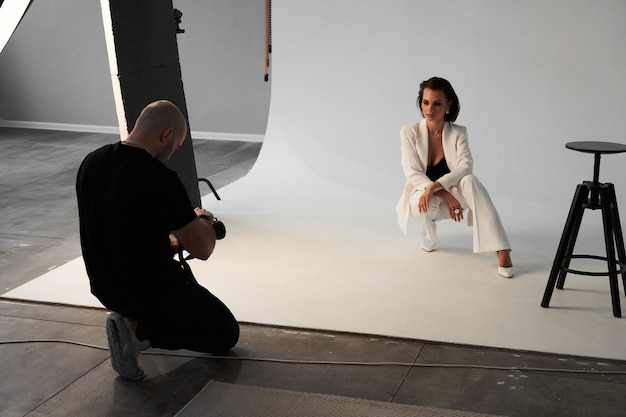 Professional male photographer taking pictures of beautiful woman model on camera in a studio