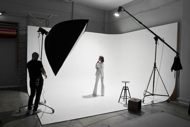 Профессиональный фотограф-мужчина фотографирует модель красивой женщины в студии
