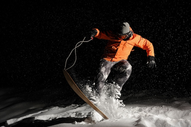 Professional male snowboarder in orange sportswear jumping on snow at night