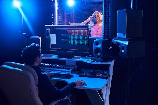 녹음 스튜디오에서 오디오 믹싱 전문 남성 사운드 엔지니어. 음악 제작 기술, 마이크에 노래하는 소녀