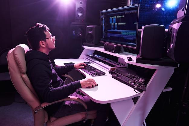 Профессиональный звукорежиссер мужского пола, микширующий аудио в студии звукозаписи. технология производства музыки, работающая на микшере