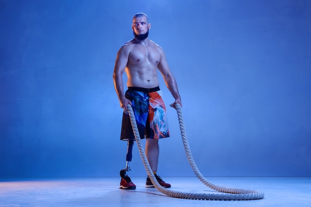 Professional male sportsman with leg prosthesis training with ropes in neon