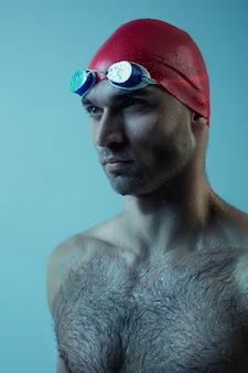 Nuotatore maschio professionista con cappello e occhiali in movimento e azione, stile di vita sano e movimento