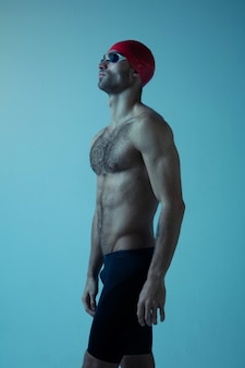 Professional male swimmer with hat and goggles in motion and action