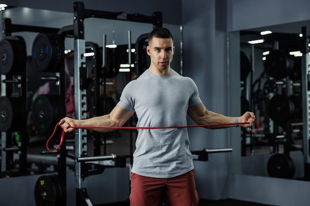 Professional male trainer doing fitness exercises with an elastic resistance band in a dark gym atmosphere