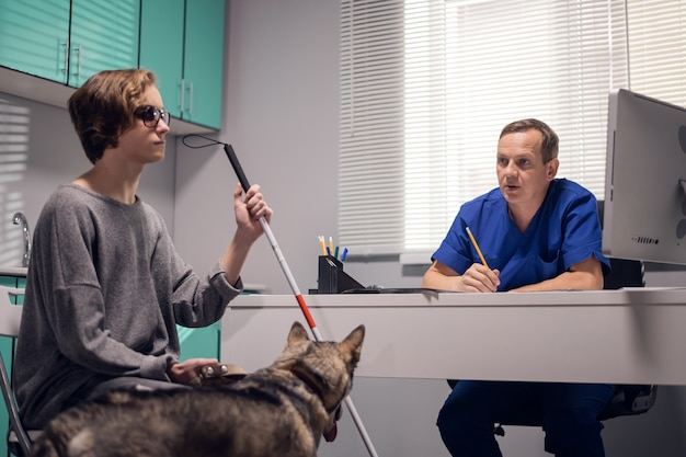 A professional male veterinarian examining a guide dog in a vet clinic.