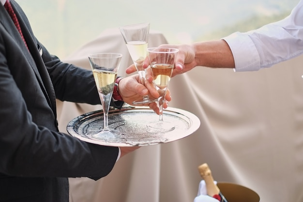 Professional male waiter in uniform serving champagne. woman taking one glass of champagne