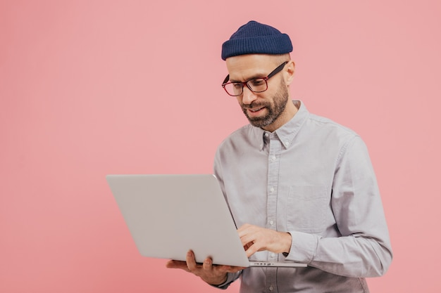 Professional male worker searches for interesting movie to watch, uses gadget, types information on laptop computer