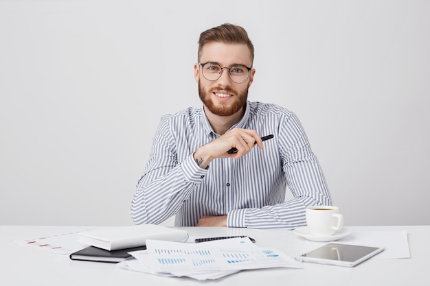 Professional male worker with thick beard and trendy hairstyle, wears round glasses and formal shirt