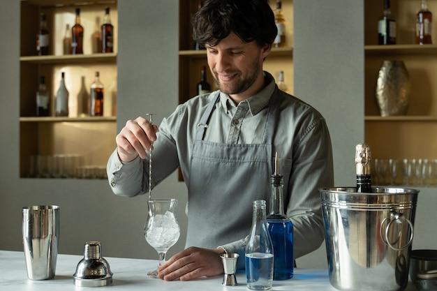 Профессиональный мужчина-бармен, помешивая лед в стакане на барной стойке