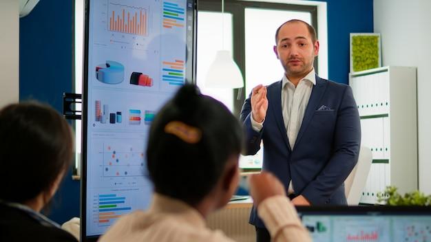 브레인스토밍 중에 회사 전략을 설명하면서 동료들과 새로운 프로젝트를 계획하는 전문 기업가입니다. 회의 중 전문 스타트업 금융 사무실에서 일하는 다양한 팀