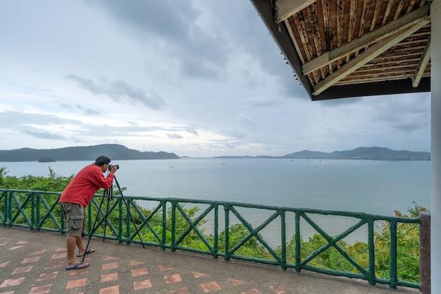 카오카드 뷰 포인트 푸켓 태국 랜드마크로 유명한 푸켓에서 일몰과 열대 해변을 볼 수 있는 풍경의 자연 경관을 촬영하는 미러리스 카메라를 설정하는 전문 남자.