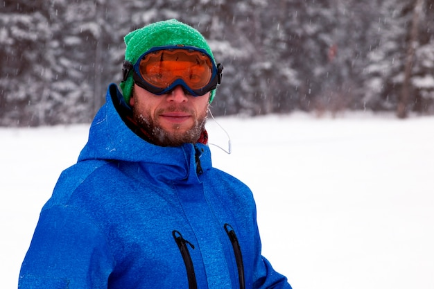 Professional man snowboarder in bright blue sportswear in snowy high mountains. concept rest apres ski
