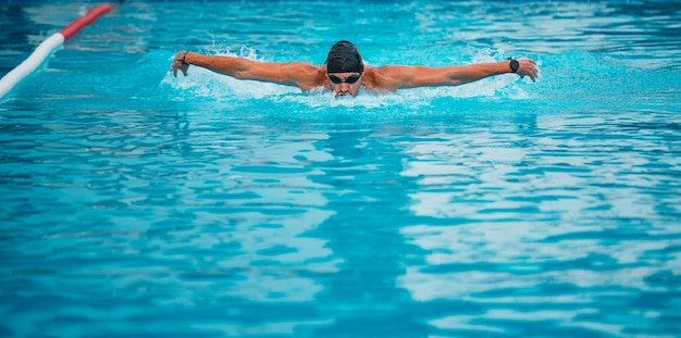 Профессиональный мужчина, плавающий в стиле бабочки в шляпе и очках у бассейна