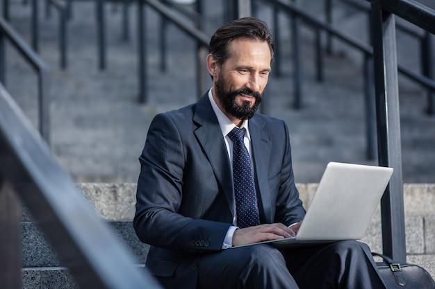 Профессиональный менеджер. приятный прилежный менеджер, использующий ноутбук во время работы в городских условиях