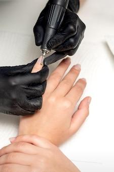 검은 장갑의 전문 매니큐어 마스터는 미용실의 특수 전기 드릴 매니큐어 도구로 큐티클을 제거합니다