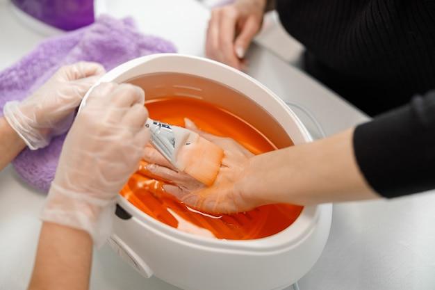 전문 매니큐어 마스터가 미용실에서 고객을 위해 손톱을하고 있습니다.