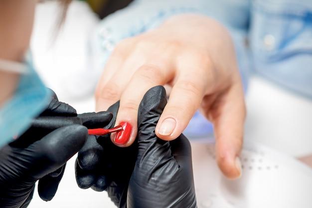 Профессиональный мастер маникюра красит женские ногти красным лаком в маникюрном салоне
