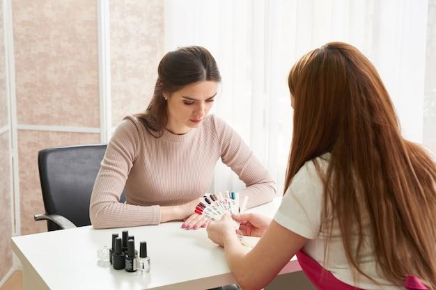 Профессиональный мастер маникюра показывает красочный лак для ногтей, чтобы проверить результат. ногтевой техник, представляющий цветовую палитру ногтевых услуг в магазине салона красоты. понятие красоты и моды.
