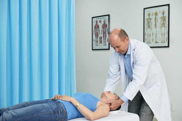Professional manual therapist massaging neck of patient