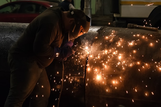 Professional mask protected welder man working on metal welding and sparks of metal at night. employee welding steel with sparks
