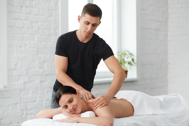 전문 마사지 치료사가 아파트에서 여성 환자를 치료하고 있습니다. 홈 마사지.