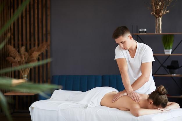 Профессиональный массажист лечит пациентку в квартире.