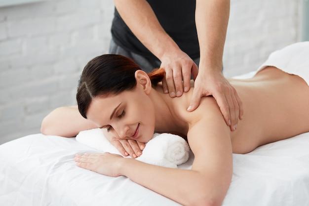 전문 마사지 치료사가 아파트에서 여성 환자를 치료하고 있습니다.
