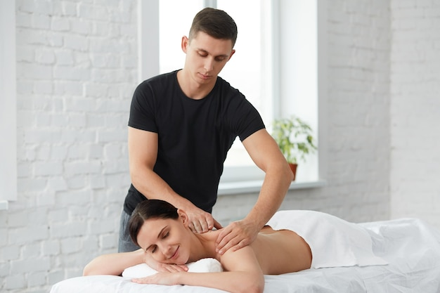 Professional massage therapist is treating a female patient in apartment. home massage.