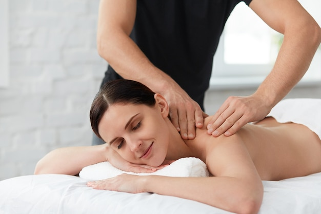 Professional massage therapist is treating a female patient in apartment.