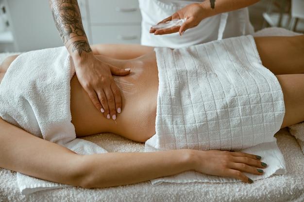 プロのマッサージ師が、現代のウェルネス サロンで若い女性のクライアントに胃マッサージをしている
