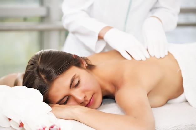 Профессиональный массажист делает массаж женской спины в салоне красоты