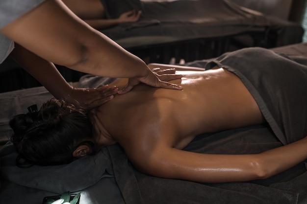 オイルで女性の背中をマッサージするプロのマッサージ師