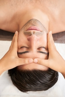 Professional masseuse doing head and face massage at wellness center. man getting face lifting massage in spa salon