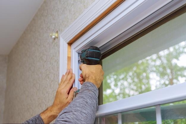 Professional master for installation of new window in house during home renovation uses an electric drill