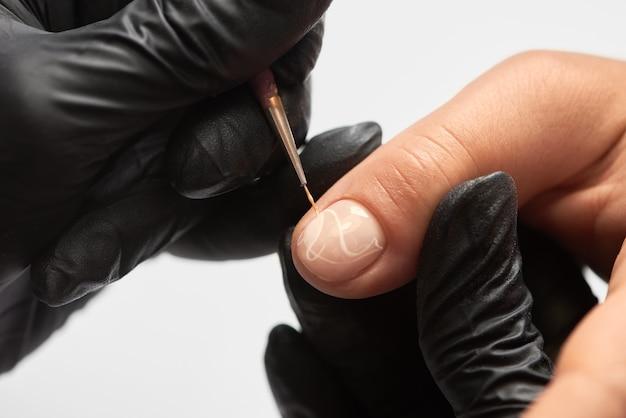 クライアントの爪に取り組んでいるプロのマスターネイリスト