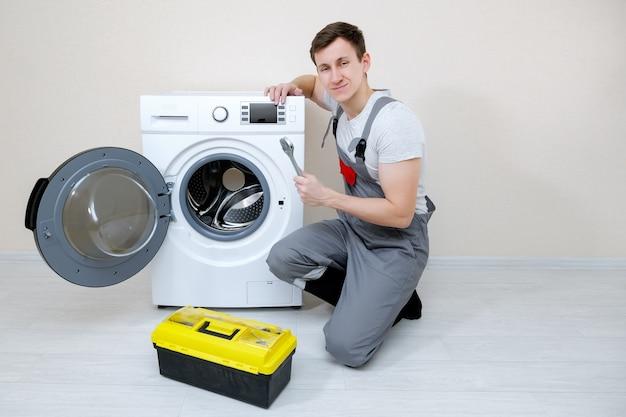 카메라를 바라보는 베이지색 벽 근처의 나무 바닥에 있는 현대적인 세탁기 근처에 렌치와 도구 상자가 있는 전문 마스터