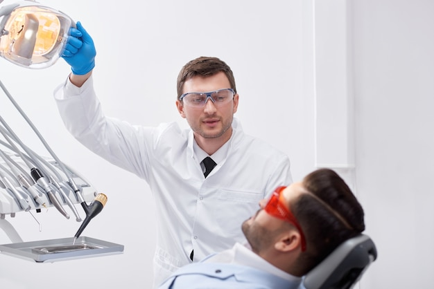Профессиональный зрелый стоматолог-мужчина работает со своим клиентом, готовясь к стоматологическому обследованию