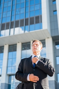 Professional mature man standing in front of building