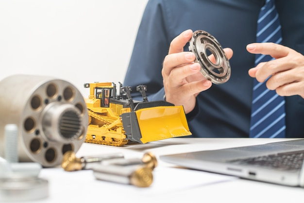 プロのメカニックエンジニアが油圧ピストンポンプのバルブプレートを検査し、オフィスでの作業中にレポートを書き込む、修理メンテナンス重機コンセプト