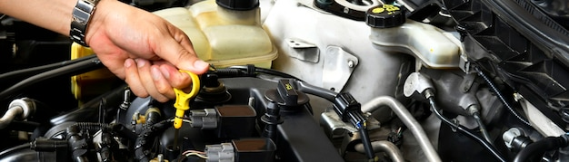 A professional mechanic is holding the oil dipstick check the oil level in car engine banner side